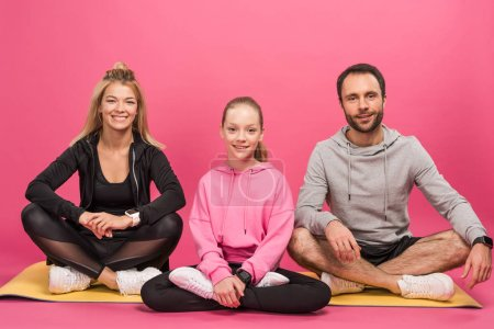 Photo for Sportive family sitting on fitness mat, isolated on pink - Royalty Free Image