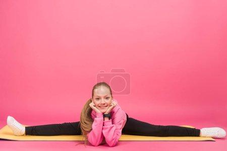 Photo pour Heureux femelle enfant faire split sur tapis de fitness, isolé sur rose - image libre de droit