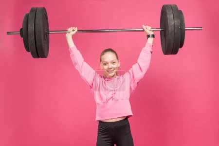 Photo for Athletic female preteen working out with barbell, isolated on pink - Royalty Free Image