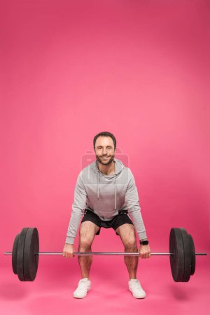 Photo for Handsome sportsman lifting barbell, isolated on pink - Royalty Free Image