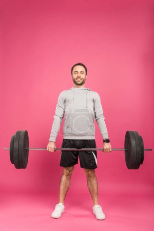 Photo for Athletic man in sportswear training with barbell, isolated on pink - Royalty Free Image