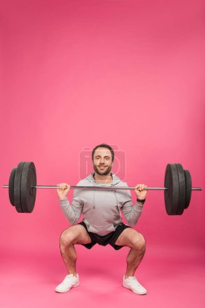 athletic man training with barbell, isolated on pink