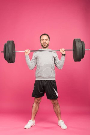 Photo for Handsome sportsman exercising with barbell, isolated on pink - Royalty Free Image