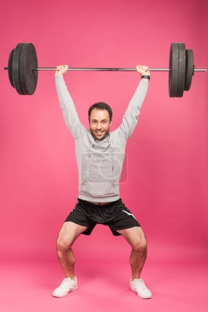 Photo for Strong sportsman training with barbell, isolated on pink - Royalty Free Image