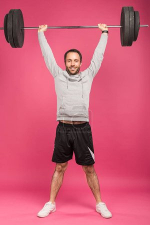 Photo for Handsome sportsman training with barbell, isolated on pink - Royalty Free Image