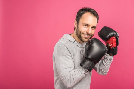 Photo for Smiling male boxer training in box gloves, isolated on pink - Royalty Free Image