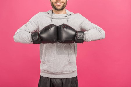 cropped view of sportsman in box gloves, isolated on pink