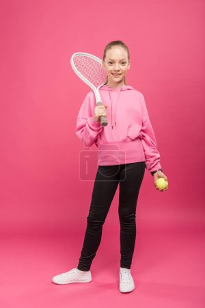 adorable kid posing with tennis racket and ball, isolated on pink