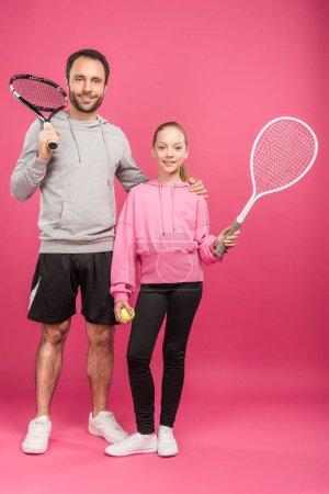 Photo pour Père et blonde fille tenant des raquettes de tennis et boule, isolé sur Rose - image libre de droit