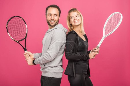 happy athletic couple holding tennis rackets, isolated on pink