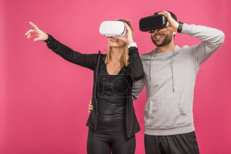 Photo for Couple gesturing and using virtual reality headsets, isolated on pink - Royalty Free Image