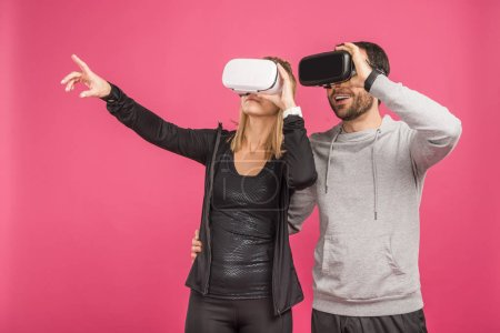 Photo for Couple using virtual reality headsets, isolated on pink - Royalty Free Image