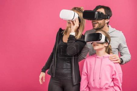 excited family using vr headsets, isolated on pink
