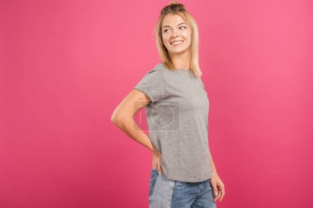 Foto de Feliz mujer atractiva posando en ropa casual, aislado en rosa - Imagen libre de derechos