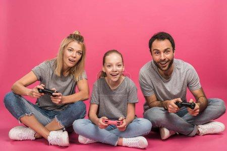 Foto de Familia muy contento de jugar video juego con joysticks, aislado en rosa - Imagen libre de derechos