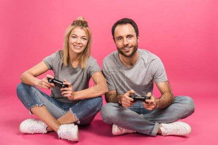 Foto de Hermosa pareja sonriente jugando video juego con joysticks, aislado en rosa - Imagen libre de derechos