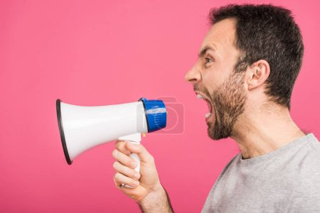 angry man yelling with megaphone, isolated on pink