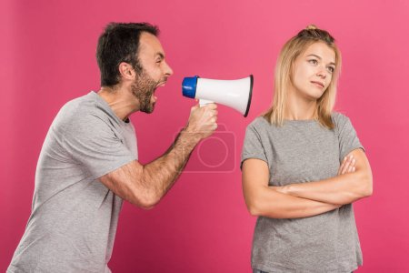 aggressive man yelling with megaphone on girlfriend, isolated on pink