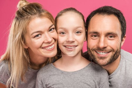 beautiful smiling parents and happy daughter, isolated on pink