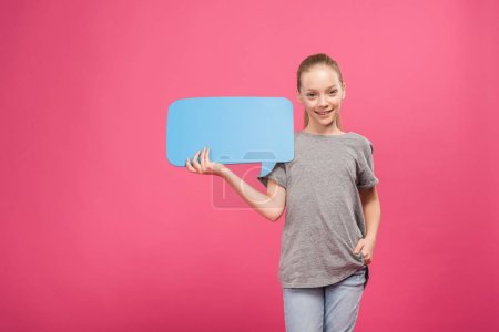blonde youngster holding blue speech bubble, isolated on pink