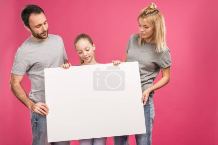 Photo for Family posing with blank placard, isolated on pink - Royalty Free Image