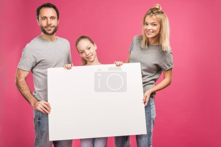 smiling family posing with blank card, isolated on pink