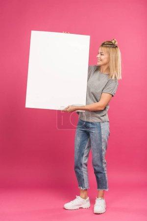Photo pour Belle femme heureuse posant avec une pancarte vide, isolée sur rose - image libre de droit