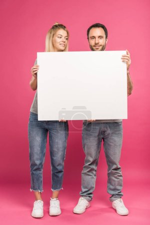 smiling couple posing with empty card, isolated on pink