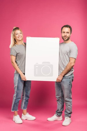 Photo for Beautiful couple posing with empty board, isolated on pink - Royalty Free Image