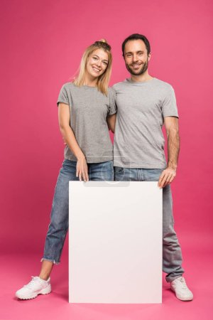 boyfriend and girlfriend posing with empty board, isolated on pink