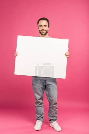 happy man posing with blank board, isolated on pink