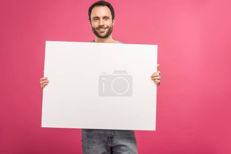 Photo for Cheerful man posing with empty board, isolated on pink - Royalty Free Image