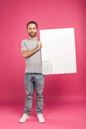 Photo pour Bel homme posant avec chambre vide, isolé sur pink - image libre de droit