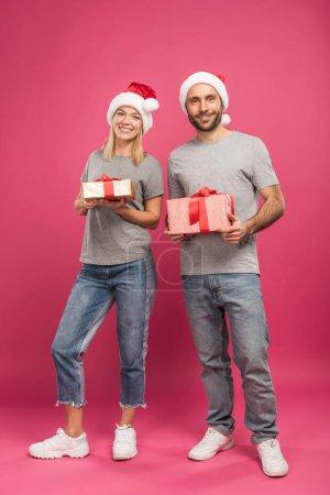 Photo pour Heureux couple en chapeaux santa holding des cadeaux de Noël sur pink - image libre de droit