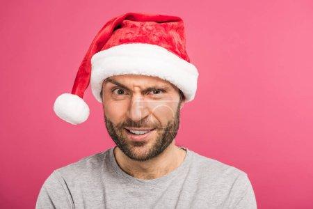 Photo pour Portrait de l'homme confus drôle en bonnet de Noel, isolé sur pink - image libre de droit