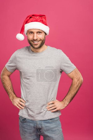 Photo pour Portrait de bel homme souriant dans bonnet au moment de Noël, isolé sur Rose - image libre de droit