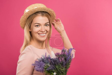 beautiful happy woman posing in straw hat with bouquet of flowers, isolated on pink