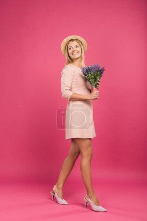 Photo pour Femme souriante en chapeau de paille tenant bouquet de fleurs, isolée sur rose - image libre de droit