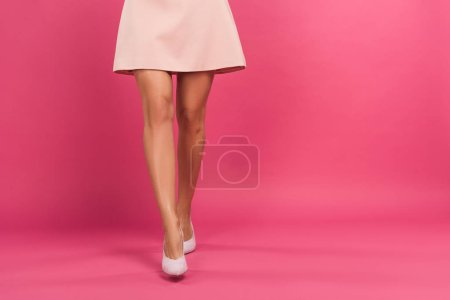 cropped view of woman in pink dress, isolated on pink