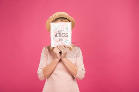 """happy woman hiding behind """"happy mothers day"""" greeting card, isolated on pink"""