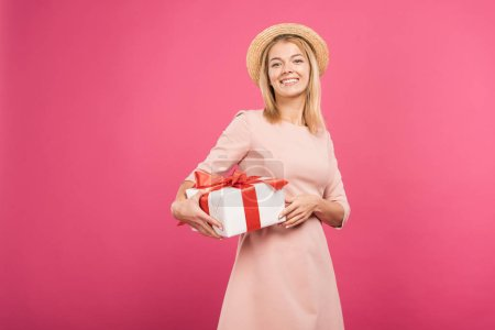 cheerful woman holding gift box isolated on pink