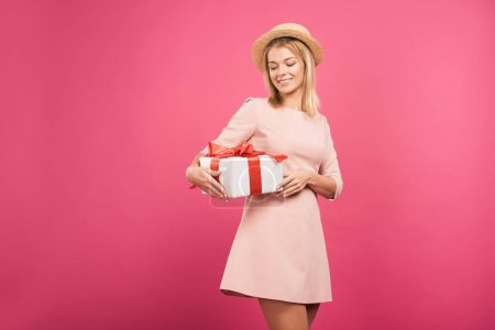 happy woman in straw hat holding present isolated on pink