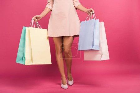 Photo pour Vue recadrée de la femme en robe tenant des sacs à provisions, isolé sur rose - image libre de droit