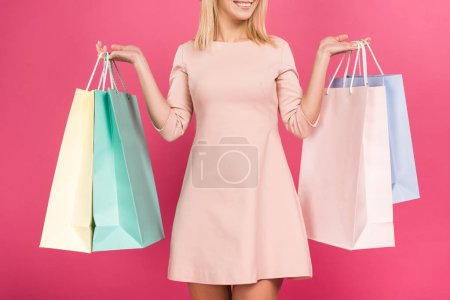 Photo for Cropped view on happy woman with shopping bags, isolated on pink - Royalty Free Image