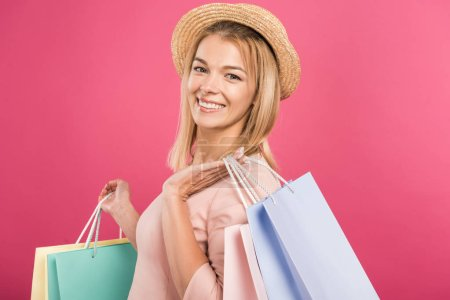customer blonde girl in straw hat holding shopping bags, isolated on pink