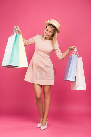 attractive female customer looking at shopping bags, isolated on pink