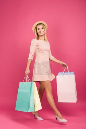 Photo for Pretty smiling woman with shopping bags, isolated on pink - Royalty Free Image