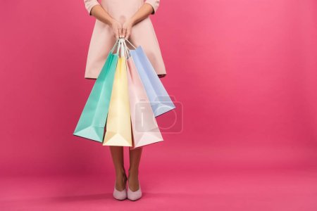 Photo for Partial view of girl with shopping bags, isolated on pink - Royalty Free Image
