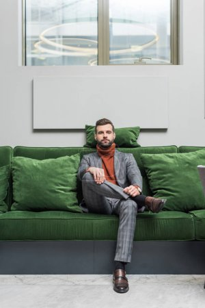Photo for Man in formal wear with legs crossed sitting on green sofa and looking at camera - Royalty Free Image