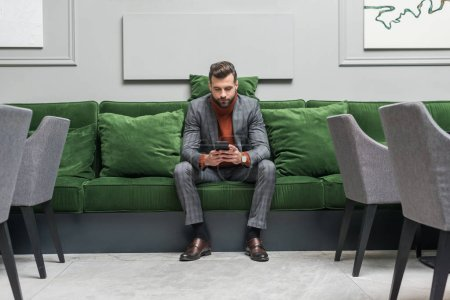 Photo for Serious handsome man in formal wear sitting on green sofa and using smartphone - Royalty Free Image
